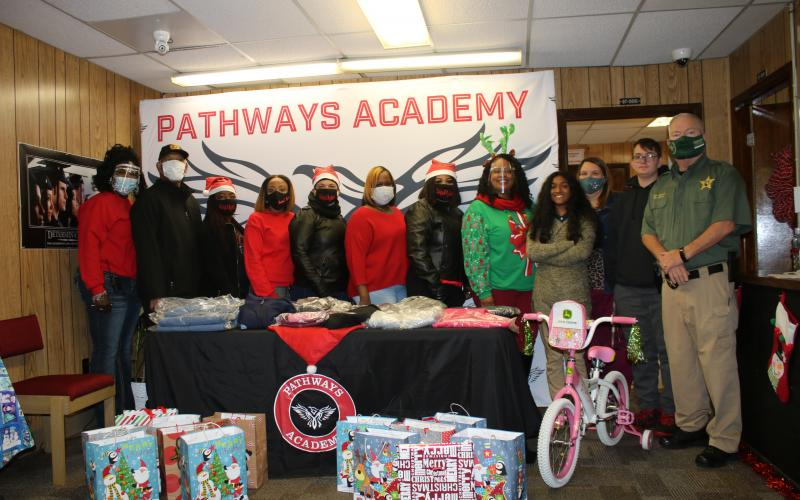 LaKasia Portee-Jones (from left), Terrence Jones, Chantal Re'Nee, Shalea Jernigan, Carol Tunsil, Jodi Watson, Tara Williams, Makeba Murphy, Neha Dabhi, Sarah Wheeler, James Jordan and CCSO Chief Deputy Joe Lucas stand behind items that were recently donated to Pathways Academy students. The students were able to take the donated items home Thursday. (TONY BRITT/Lake City Reporter)