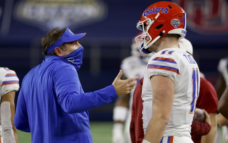 Florida coach Dan Mullen talks with quarterback Kyle Trask after Trask threw a pass into the end zone that was intercepted by Oklahoma's Woodi Washington during the first half of the Cotton Bowl on Wednesday in Arlington, Texas. (RON JENKINS/Associated Press)
