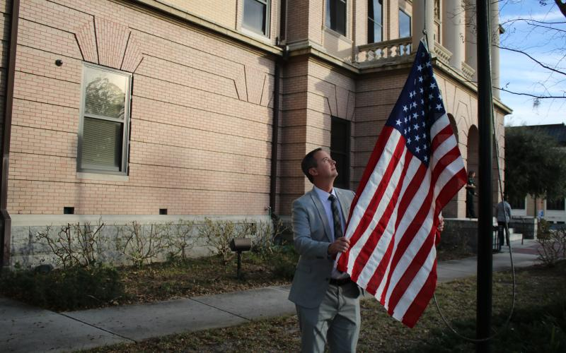 Jay Swisher, Columbia County Clerk of Court, hoists a flag over the Columbia County Courthouse Wednesday that was flown over the U.S. Capitol. (TONY BRITT/Lake City Reporter)