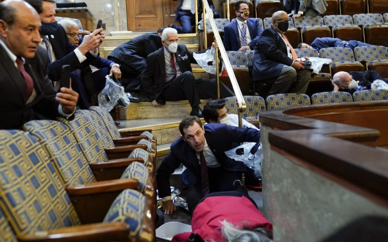 People shelter in the House gallery as protesters try to break into the House Chamber at the U.S. Capitol on Wednesday in Washington. (ANDREW HARNIK/Associated Press)